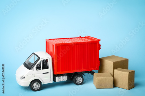 Obraz Toy truck with boxes on blue background, space for text. Logistics and wholesale concept - fototapety do salonu