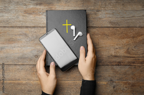 Fotomural  Woman with Bible, phone and earphones at wooden table, top view