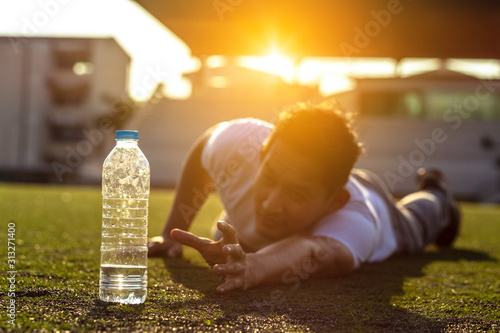Fotografie, Obraz Thirsty man on grass at sport stadium reach for a bottle of pure water