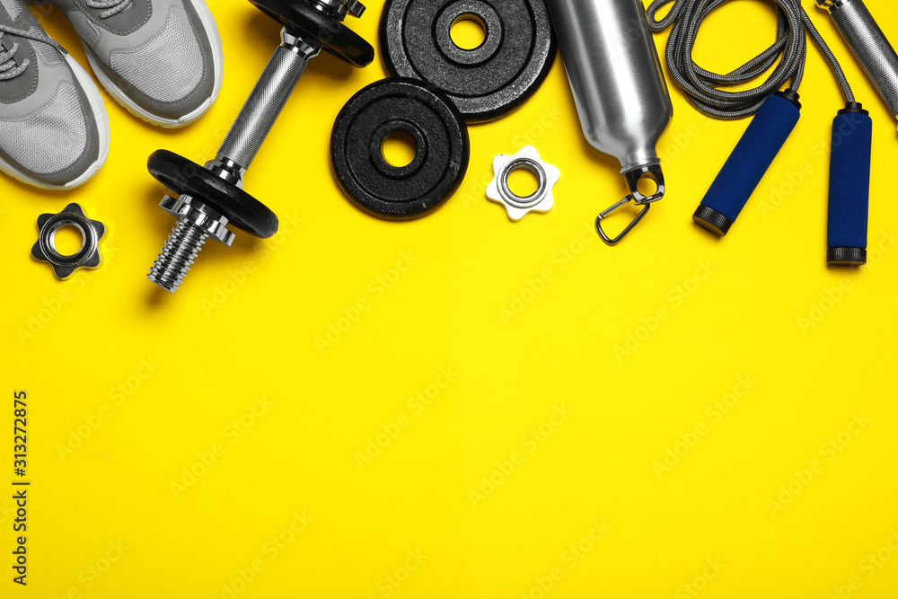 Fototapeta Gym equipment on yellow background, flat lay. Space for text
