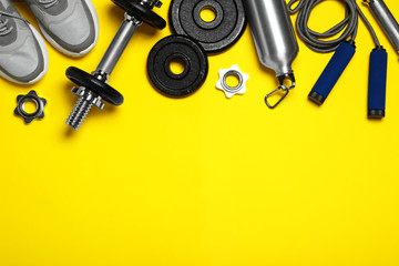 Gym equipment on yellow background, flat lay. Space for text