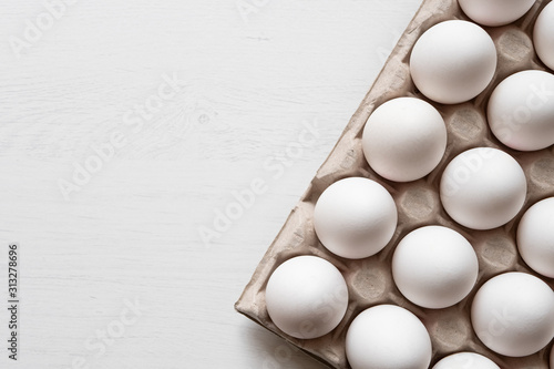 Canvas Print Detail of white chicken eggs in paper tray.