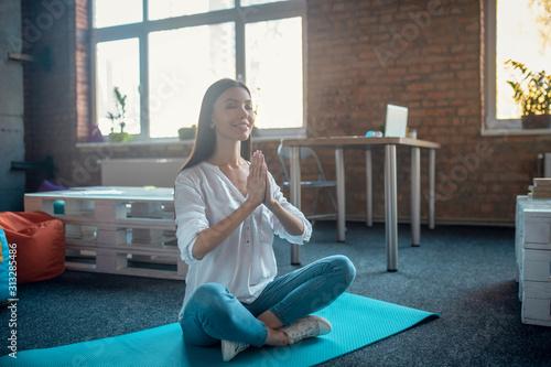 Fototapeta Beautiful peaceful woman sitting in the lotus pose obraz na płótnie