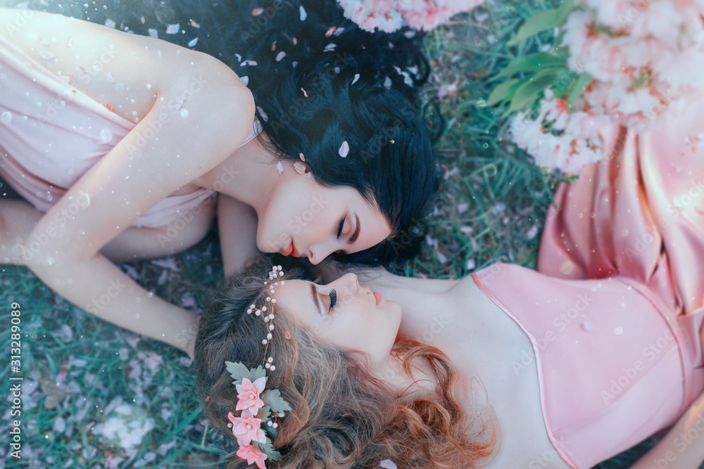 Fototapeta portrait two young women lie cuddling on grass in spring garden, luxurious long curly hair strewn with flowers rose petals. Attractive face gentle makeup. Different sisters. Natural cosmetics concept