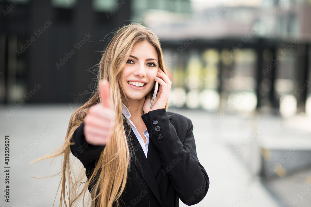 Fototapeta Smiling business woman talking on the phone and thumbs up
