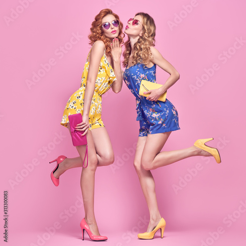 Two Young carefree Woman in stylish playsuit having fun. Beautiful fashionable model girl in trendy summer outfit. Graceful friends with fashion hairstyle, make up on pink. Creative funny concept Wall mural