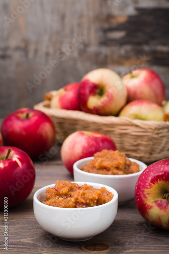 Fresh applesauce in bowls and red apples on a wooden table Canvas Print
