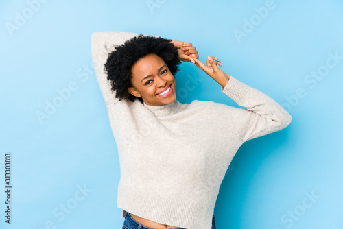 Obraz Middle aged african american woman against a blue background isolated stretching arms, relaxed position. - fototapety do salonu