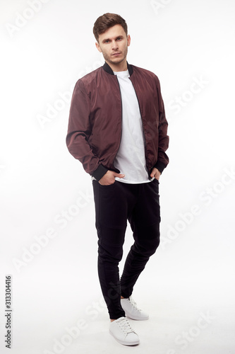 Canvas-taulu Young european man in white sweater and black pants, red bomber jacket posing on white background