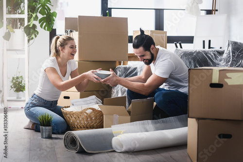 Happy young couple unpacking or packing boxes and moving into a new home Canvas Print