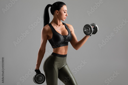 Carta da parati Fitness woman doing exercise for biceps on gray background