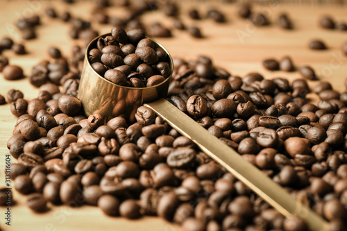 Fotografía Coffee beans are poured on a wooden surface and in the middle is a coffee spoon