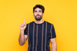 Young handsome man with beard over isolated yellow background pointing with the index finger a great idea