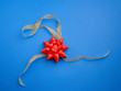 canvas print picture - golden silk thin ribbon twisted and red shiny bow on a blue background