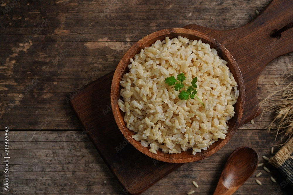 Fototapeta Bowl of cooked Whole grain brown rice  on wooden background overhead view