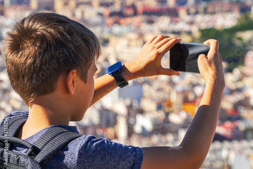 Boy with smartphone in his hands takes photo of Alicante city from Santa Barbara Canvas Print