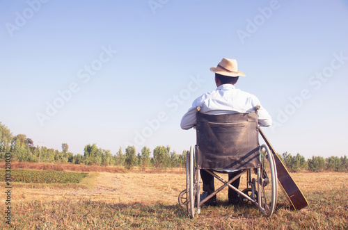 Young disabled man and guitar with field background Fototapet