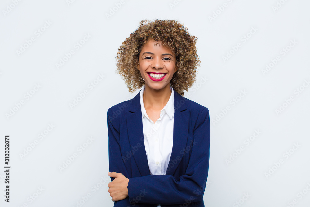 Fototapeta young woman african american laughing shyly and cheerfully, with a friendly and positive but insecure attitude against flat wall