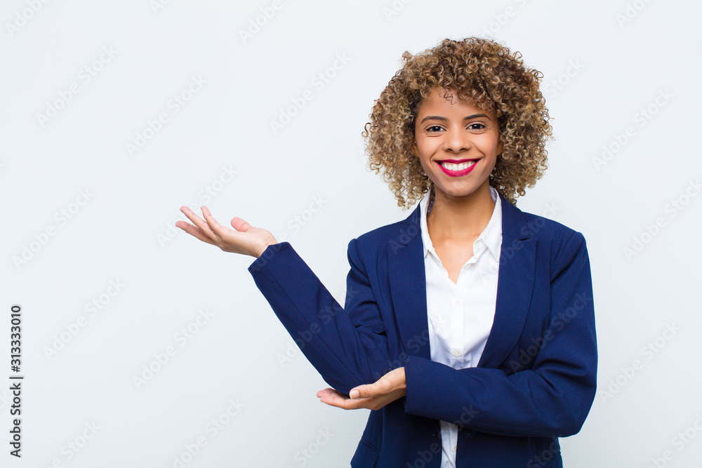 Fototapeta young woman african american smiling proudly and confidently, feeling happy and satisfied and showing a concept on copy space against flat wall