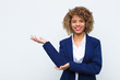 Leinwanddruck Bild - young woman african american smiling proudly and confidently, feeling happy and satisfied and showing a concept on copy space against flat wall