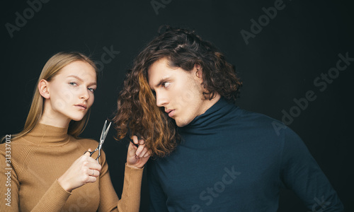Hairdresser girl going to cut off long wavy bleached dry hair of customer man. Man hair style, wellness and fashion. Female with scissors going to do amazing man haircut. Hair salon concept.