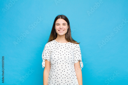 young pretty woman looking happy and goofy with a broad, fun, loony smile and ey Wallpaper Mural