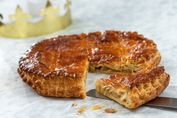 Epiphany Twelfth Night cake french galette des rois made of puff pastry, slice apart with the charm inside, open crown leaning beside