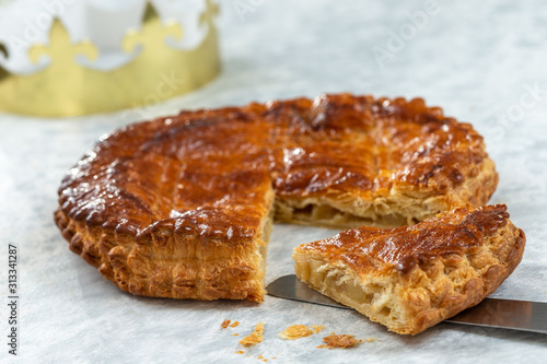 Fototapeta Epiphany Twelfth Night cake french galette des rois made of puff pastry, slice apart with the charm inside, open crown leaning beside obraz