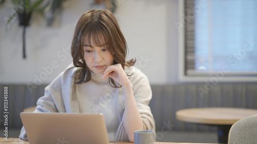 Photo カフェでノートパソコンを操作している女性
