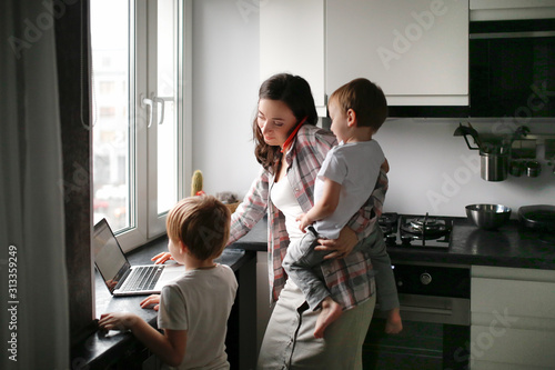 Fototapeta Busy mom with two children works on laptop kitchen obraz