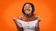 canvas print picture - Joyful Girl Celebrating Success Shaking Fists Over Orange Background, Studio