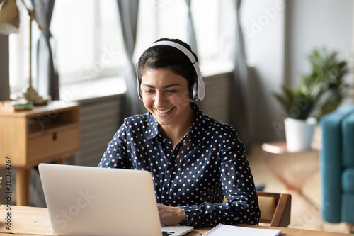 Obraz Happy indian young girl wear headphones watching listening online course - fototapety do salonu