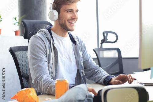 Fotografía  Smiling young man in casual clothing using computer, streaming playthrough or walkthrough video