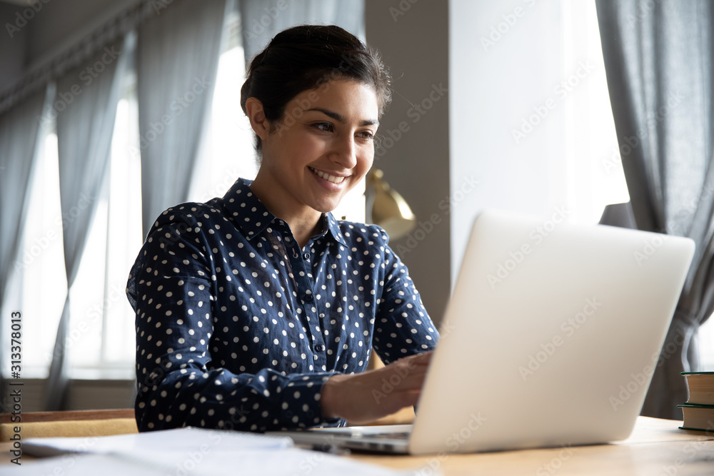 Fototapeta Smiling indian girl student professional typing on laptop at table