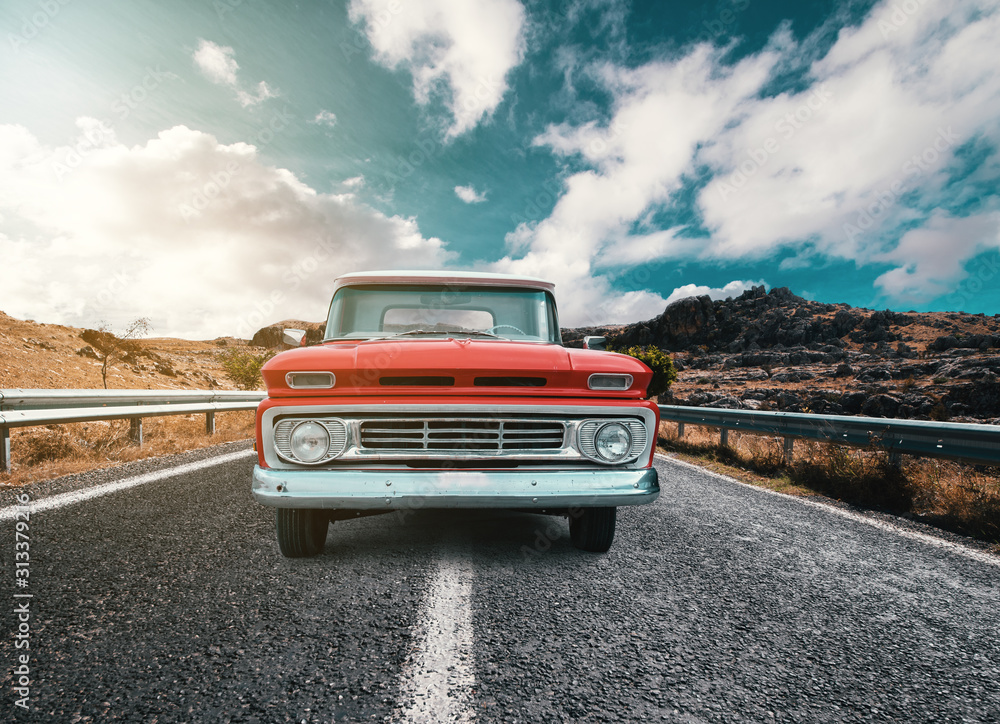 Fototapeta A Classical automobile on a journey on the country raod against the cloudy and blue sky