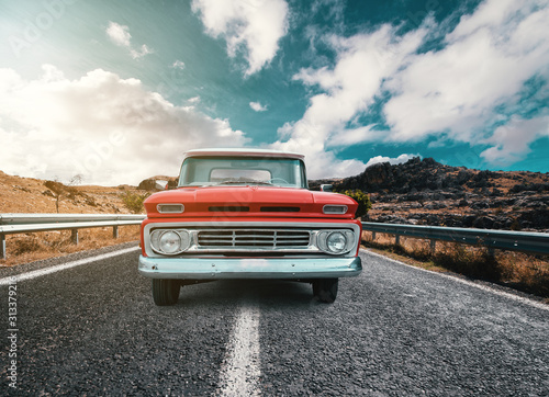 obraz PCV A Classical automobile on a journey on the country raod against the cloudy and blue sky