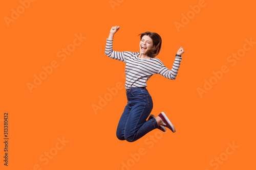 Full length portrait of excited pretty woman with brown hair in casual shirt and denim jumping celebrating victory, raising fists showing yes gesture Fototapeta