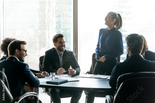 Happy diverse colleagues laugh brainstorming at meeting together