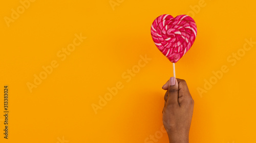 Fotografia Black female hand holding heart shaped lollipop on orange background