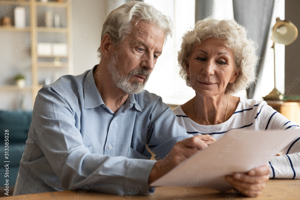 Fototapeta Mature couple read medical insurance terms seated at table indoors