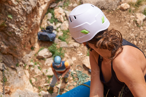 Photo A rock climbing girl in helmet looking down to her belaying buddy