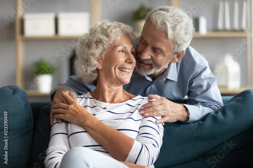 Happy married elderly couple enjoy pleasant time together indoors Canvas Print