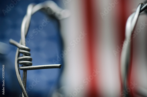 Obraz Barbed wire and United States of America flag , immigration stock photo. - fototapety do salonu