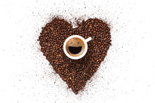 Heart Made From Coffee Beans And Ground Coffee On A White Background. In The Center Is A Cup, In A Cup From Coffee Foam A Happy Smiling Face. Invigorating Drink Concept