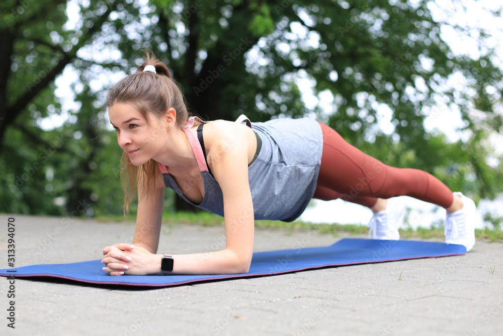 Fototapeta Sport girl doing plank exercise outdoor in the park warm summer day.