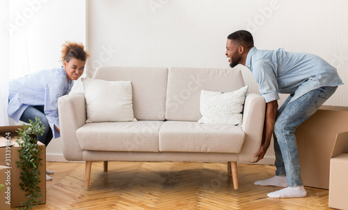 Couple Lifting Sofa Standing In Empty Room After Moving House Fototapet
