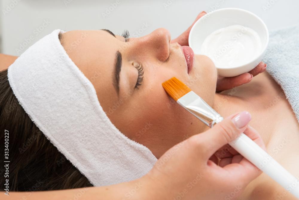 Fototapeta Kobieta w spa. Pielęgnacja cery, nakładanie maski w salonie kosmetycznym.