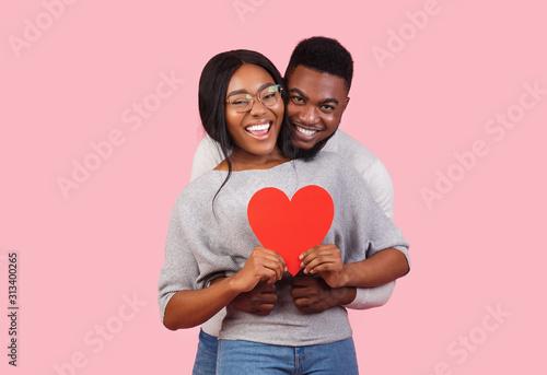 Obraz Joyful african couple holding big red heart together - fototapety do salonu