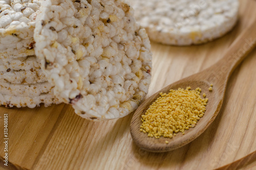 Valokuva Soy lecithin in a wooden spoon on a wooden backgroundand round multigrain rice cakes