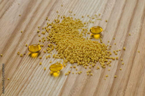 Photo Soy lecithin granules and gel pills capsule on a wooden background